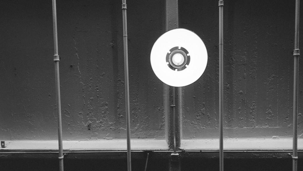Fotografía en B/N de una bombilla en un techo industrial