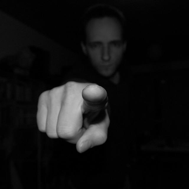 Primer plano de una mano en gesto acusador con la persona al fondo. B/N