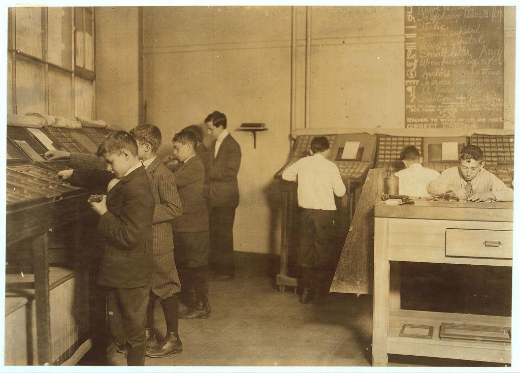Foto en sepia de un grupo de niños aprendiendo a colocar tipos móviles de imprenta en sus cajas correspondientes.
