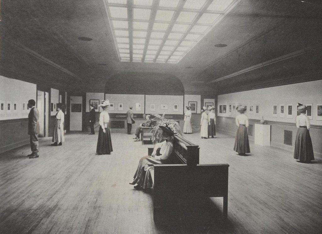 Fotografía en B/N de la sala de exposiciones en el 4º piso de la Biblioteca Pública de Newark. Muestra a diferentes visitantes (al menos 3 hombres y 8 mujeres) visitando una exposición de estampas.