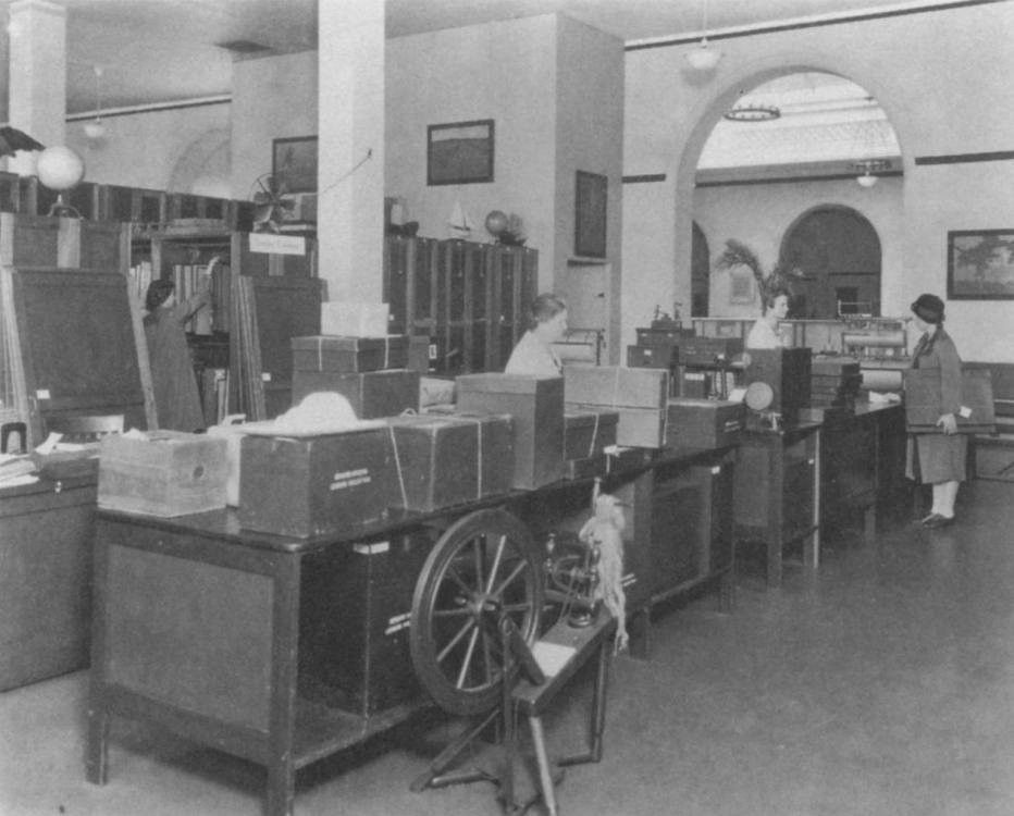 Foto en B/N de empleados del Museo de Arte de Newark preparando lotes de préstamo para centos educativos c. 1926.