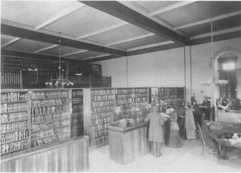 Foto en B/N de la bilbioteca pública de Denver en 1893 con diversas personas realizando gestiones  y J.C. Dana al mostrador. Pueden verse los pasillos de estanterías al fondo, de libre acceso.