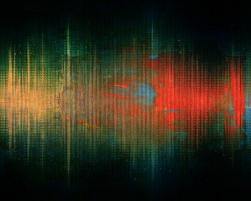 Representación gráfica de una onda sonora en tonos amarillos, verdosos y rojos sobre fondo negro en forma de espectro.